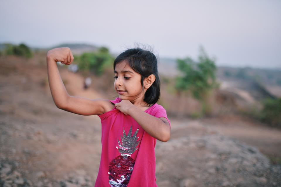Preschool age girl showing her muscles