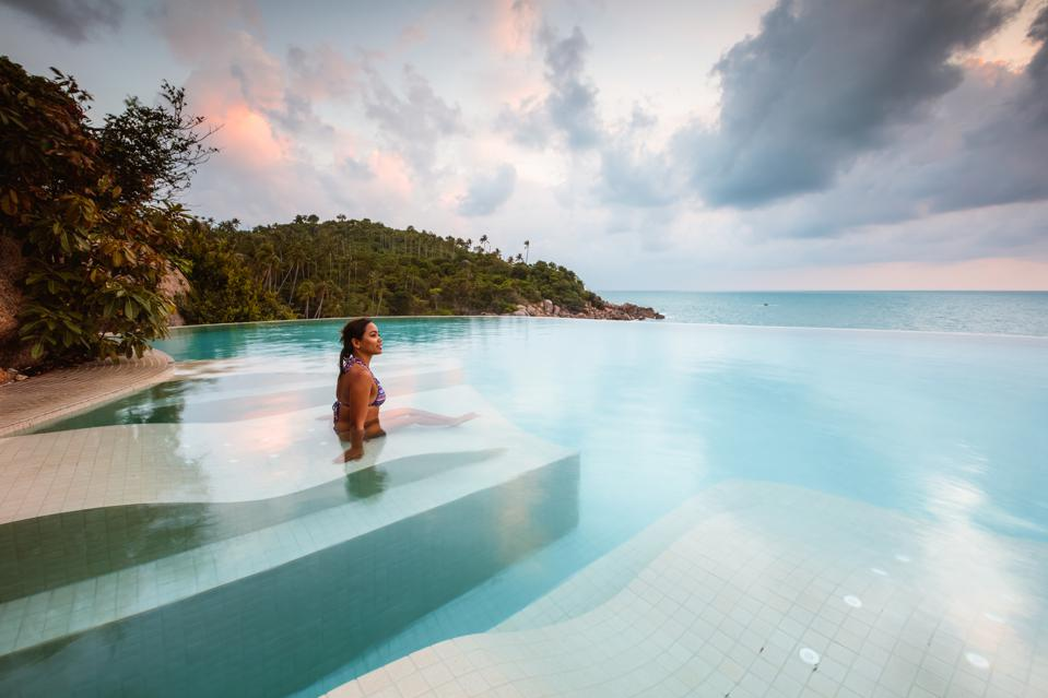 Beautiful woman in an infinity pool at sunset, Thailand
