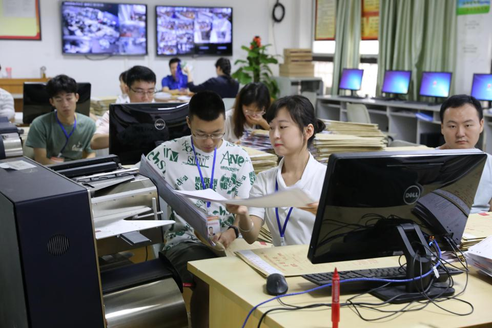 Staff Members Scan Exam Papers For Gaokao In Haikou