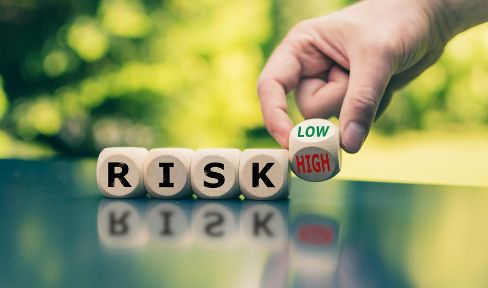 Symbol for reducing a risk. Cubes form the word ″RISK″ while a hand turns a cube and changes the word ″high″ to low″ (or vice versa).