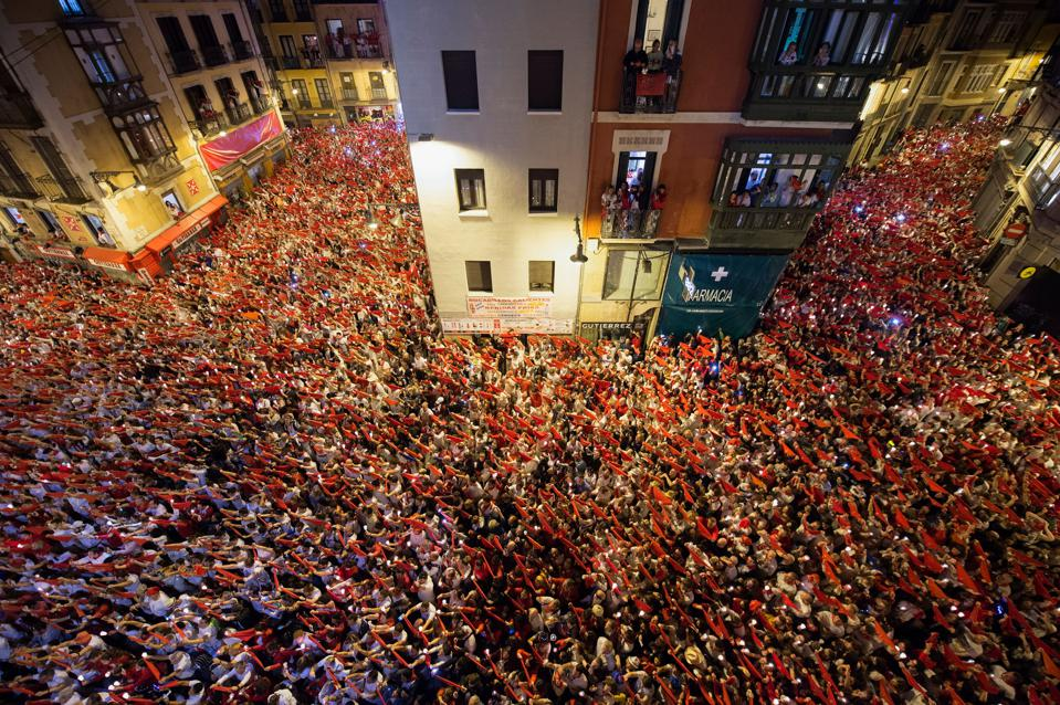 Revellers raise red scarves and candles as they sing the song 'Pobre de Mi', marking the end of the San Fermin festival in Pamplona, northern Spain on July 15, 2019.