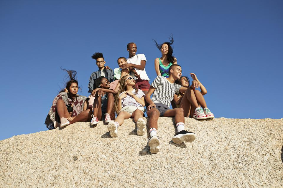 Multi-ethnic friends sitting together on rock