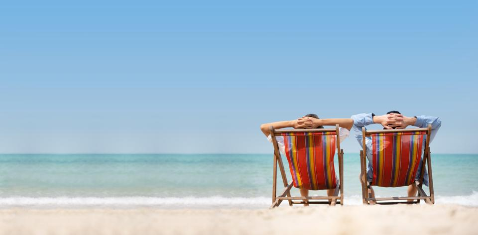 Couple relaxing on chair beach over sea background.