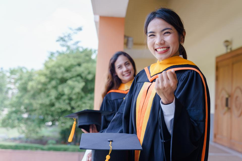 Female university graduates celebrate happily after completed and received a diploma degree. The female graduates express congratulations with each other.