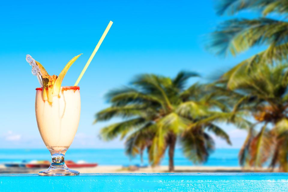 Refreshing pina colada cocktail against amazing beach background with palms and ocean. Summer vacation concept.