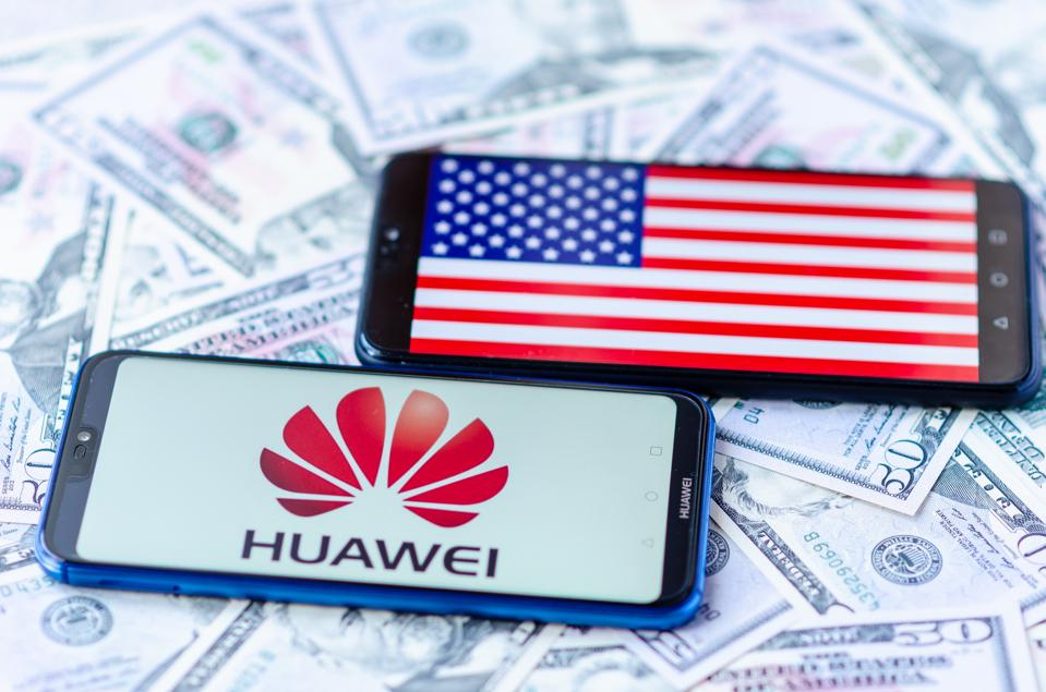 The close up photo of two mobile phones on dollar bills with Chinese HUAWEI logo and American flag. The conceptual editorial photo shows US China trade war.