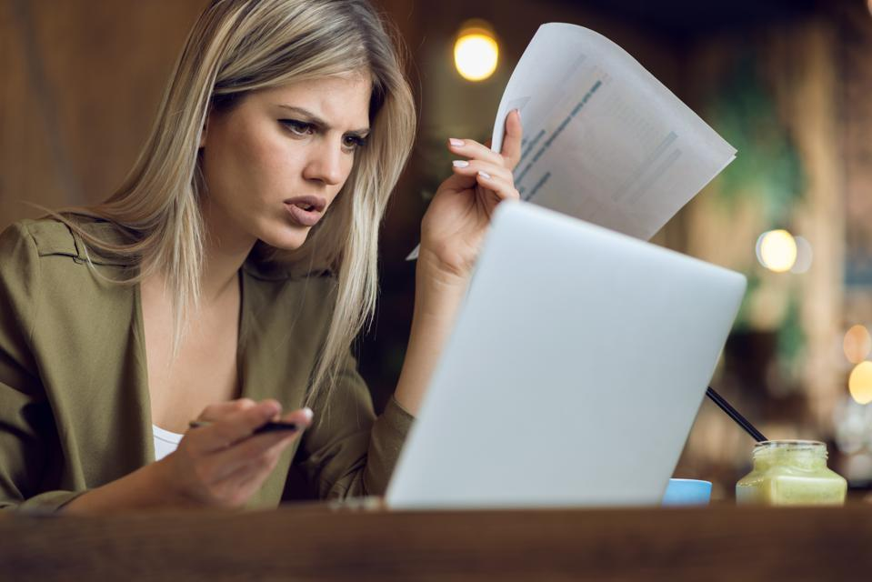 Worried businesswoman working on reports in a cafe