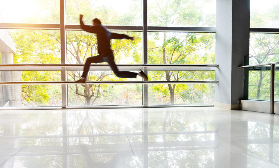 Man jumping in lobby of an office building.