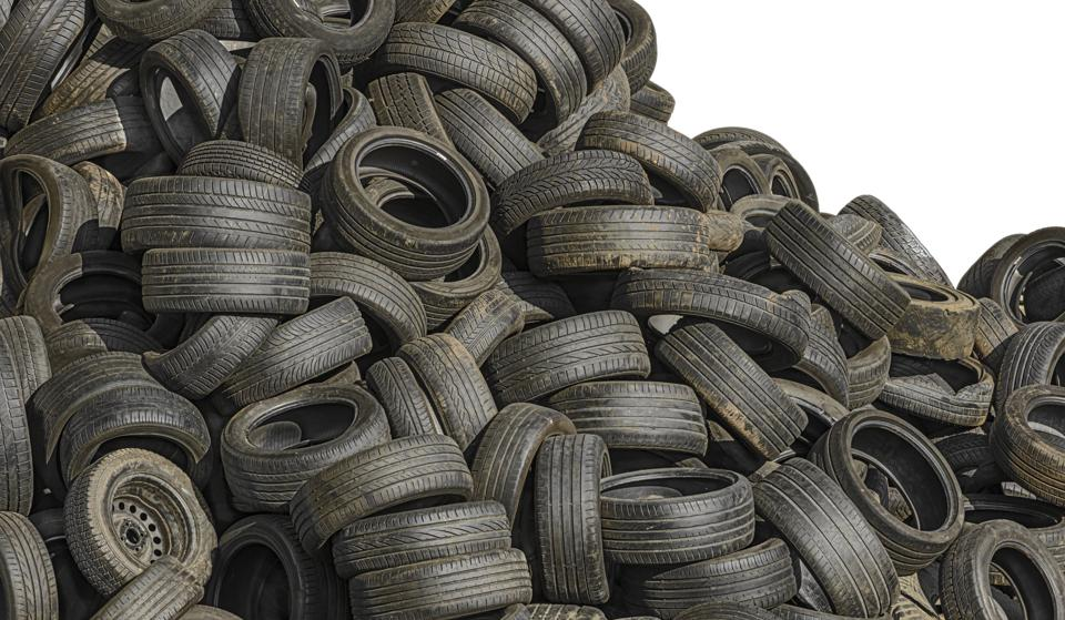 Recycling: Pile of old used scrap tyres at junkyard, isolated