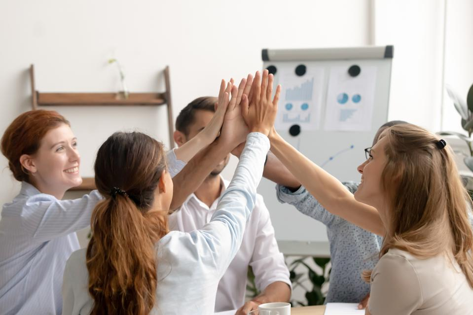 Happy motivated business team giving high fives after successful teamwork.