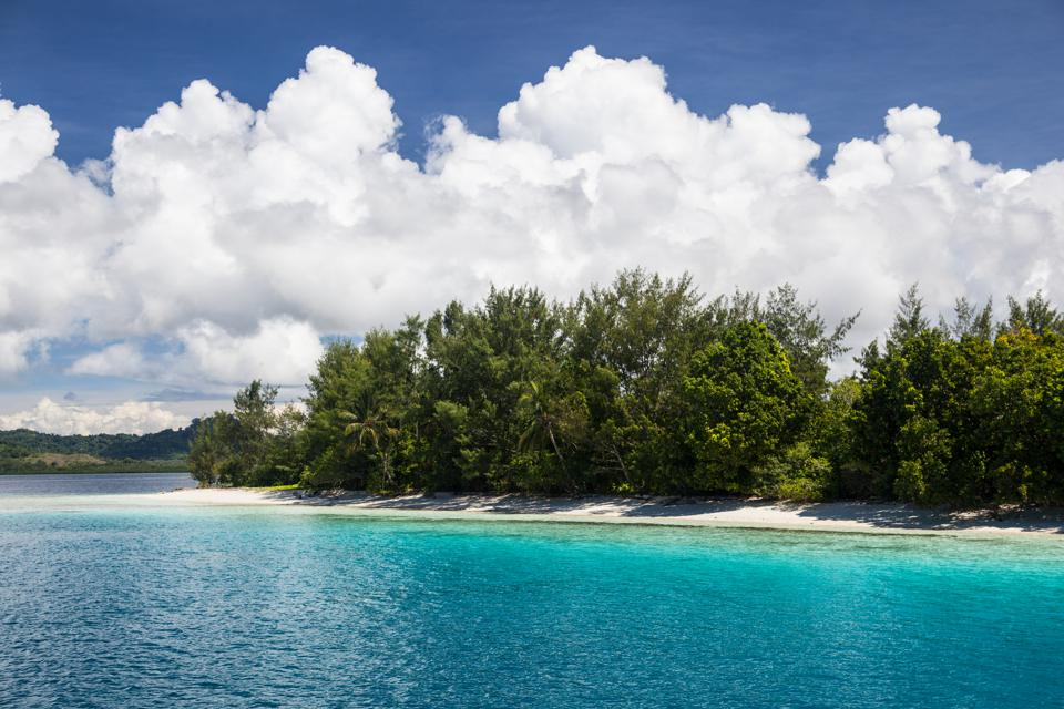 Bright sunlight shine on a remote beach and colorful lagoon in the Solomon Islands.
