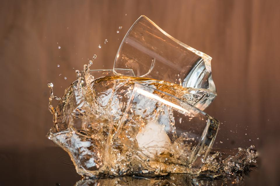 Two glasses of whiskey with ice hit and break, pouring a lot of spray and drops