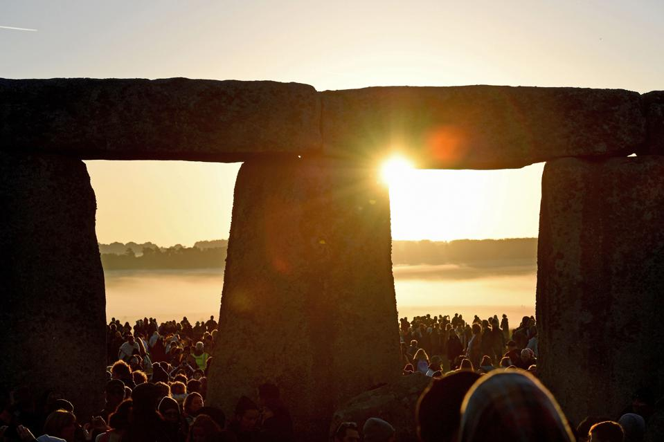 Visitors celebrate summer solstice and the dawn of the longest day of the year at Stonehenge on June 21, 2019 in Amesbury, England. (Photo by Finnbarr Webster/Getty Images)