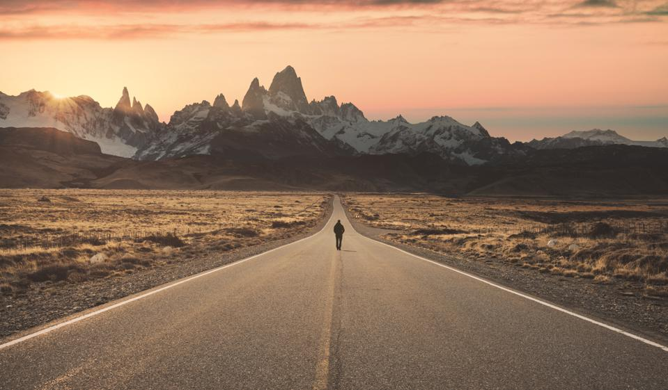 Man walking alone on the road to Fitz Roy, Patagonia Argentina