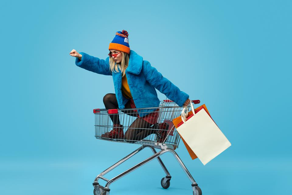 Young woman with shopping bags riding trolley