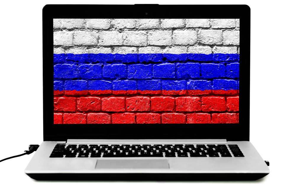 Isolated laptop with the Russian flag painted on a brick wall on the screen
