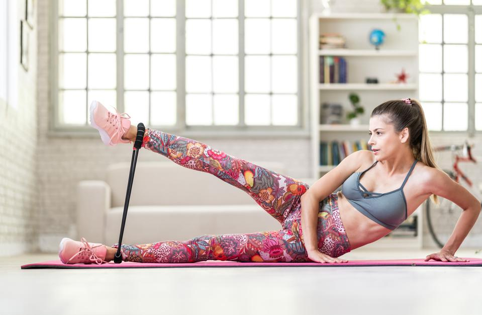 Woman uses resistance band at home. Here are 10 at-home cardio workout gift ideas for Mother's Day.