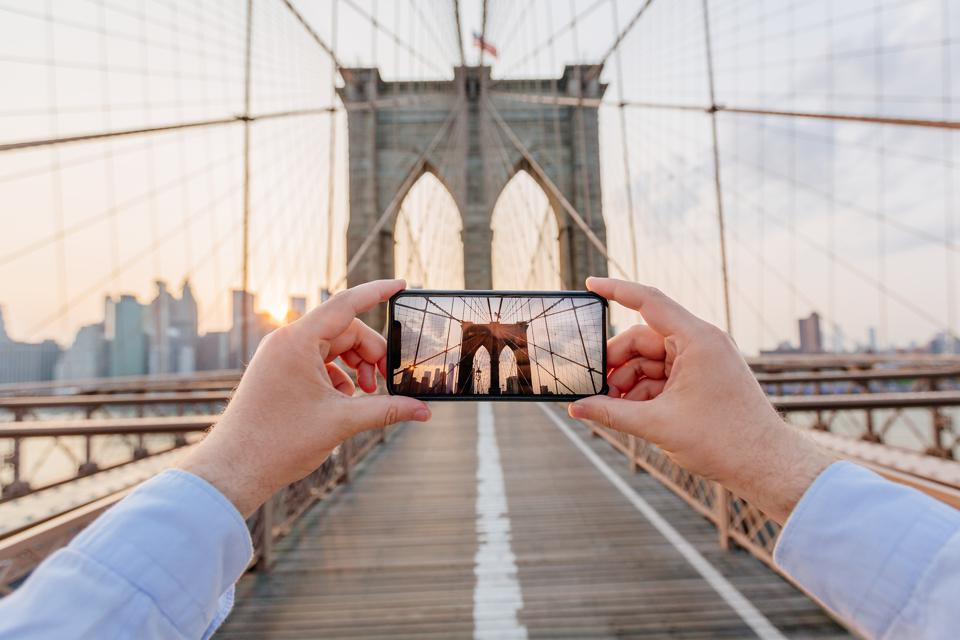 Personal perspective view of a man photographing Brooklyn Bridge using smartphone, New York, USA