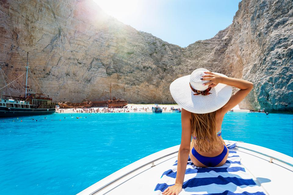 Woman on a boat enjoys the view to the shipwreck beach, Navagio in Zakynthos, Greece