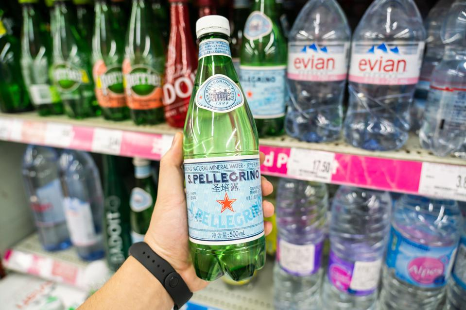 A customer holds a bottle of SanPellegrino sparkling natural...