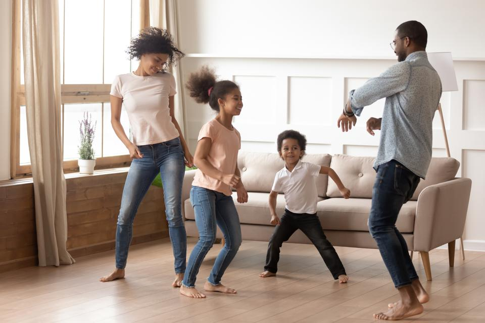 Happy funny active african family of four dancing at home