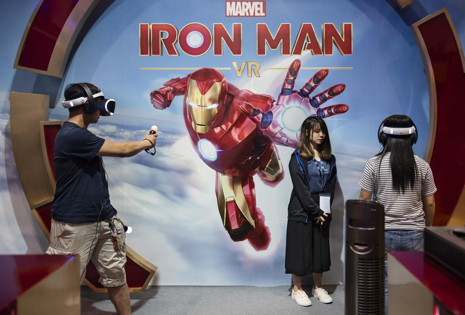 Visitors are seen playing a Marvel Iron man game with a...