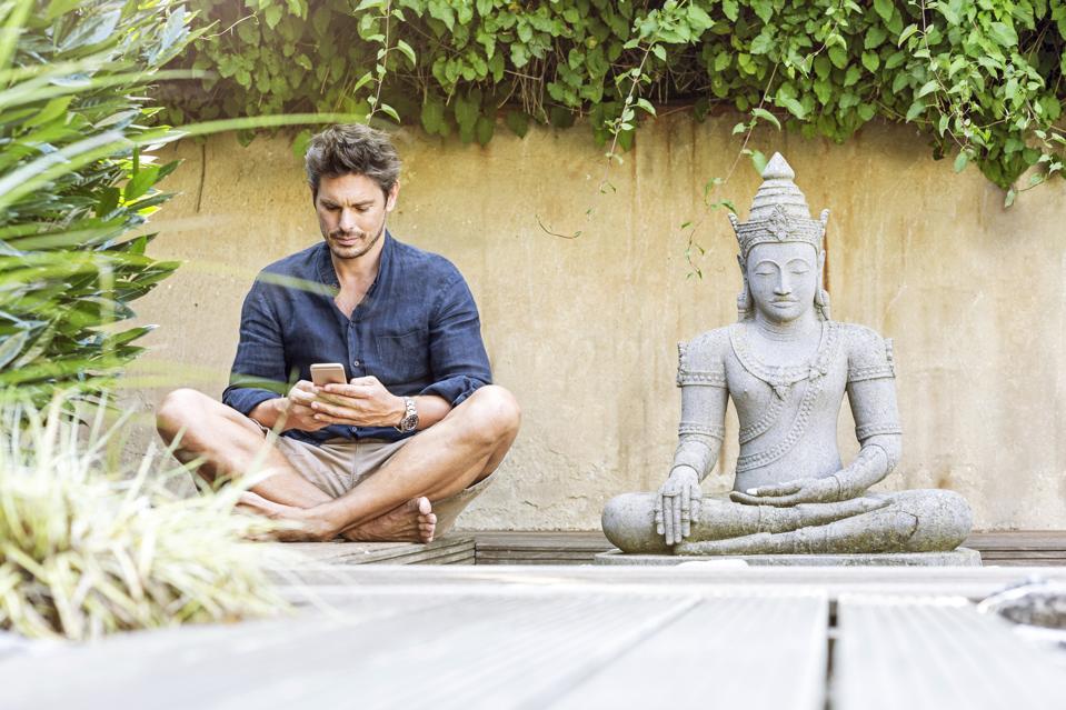 Man sitting cross-legged next to Buddha statue in a Zen garden, using smartphone
