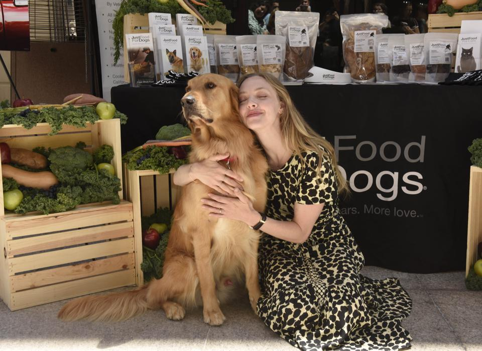 young woman with long hair cuddles a golden retriever dog