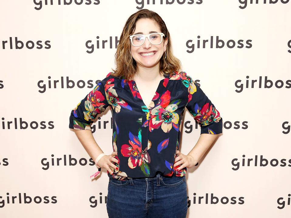Gaby Dunn, a woman wearing glasses and jeans, standing in front of a banner printed with ″girlboss″