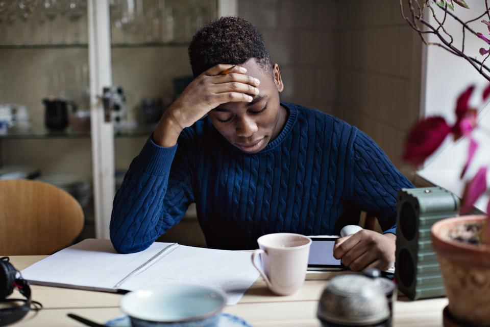 Worried teenage boy with head in hand studying at home