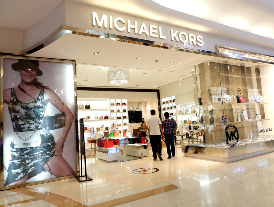 Visitors walk past Michael Kors - Luxury Leather store at...