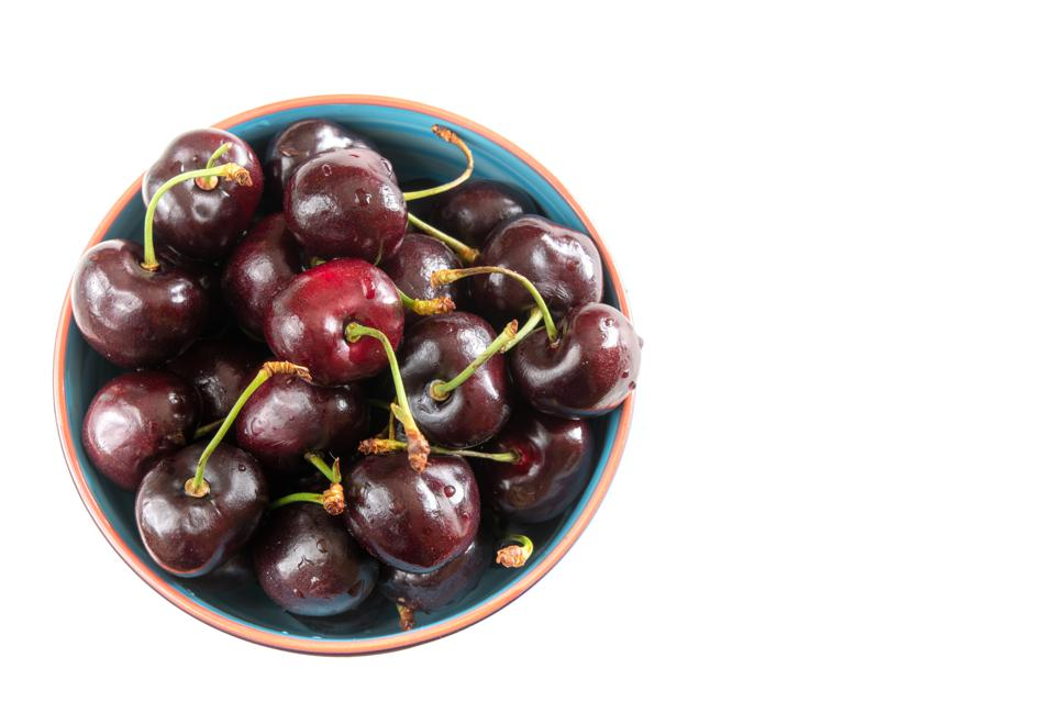 Red cherries served in a bowl over a white background.  The...