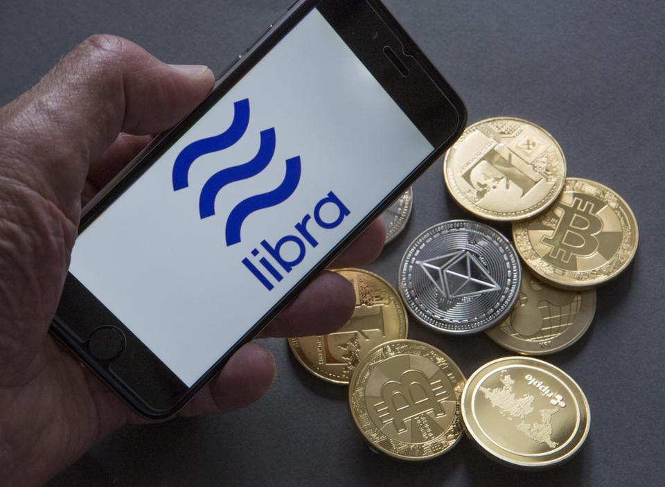 Facebook and the digital currency libra. The photo shows the libra logo on the display of a mobile phone and coins (physical) of the crypto currencies Bitcoin, Ripple, Ethereum and Litecoin.