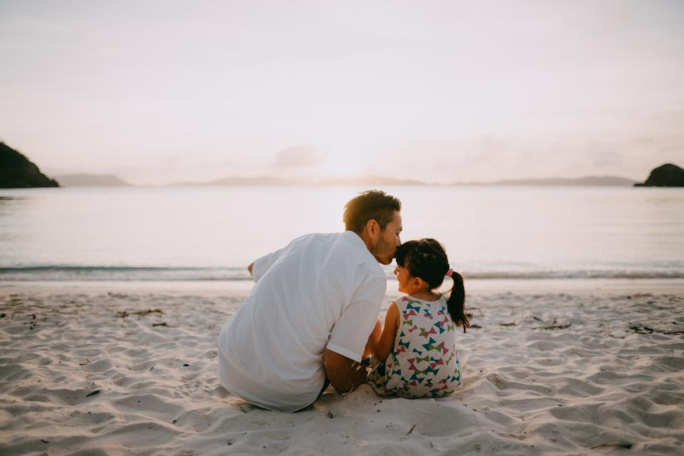 Father kissing daughter on beach at sunset, Okinawa, Japan
