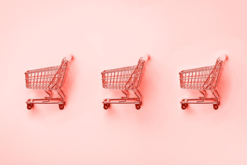 Shopping cart on trendy coral color background. Shop trolley at supermarket.