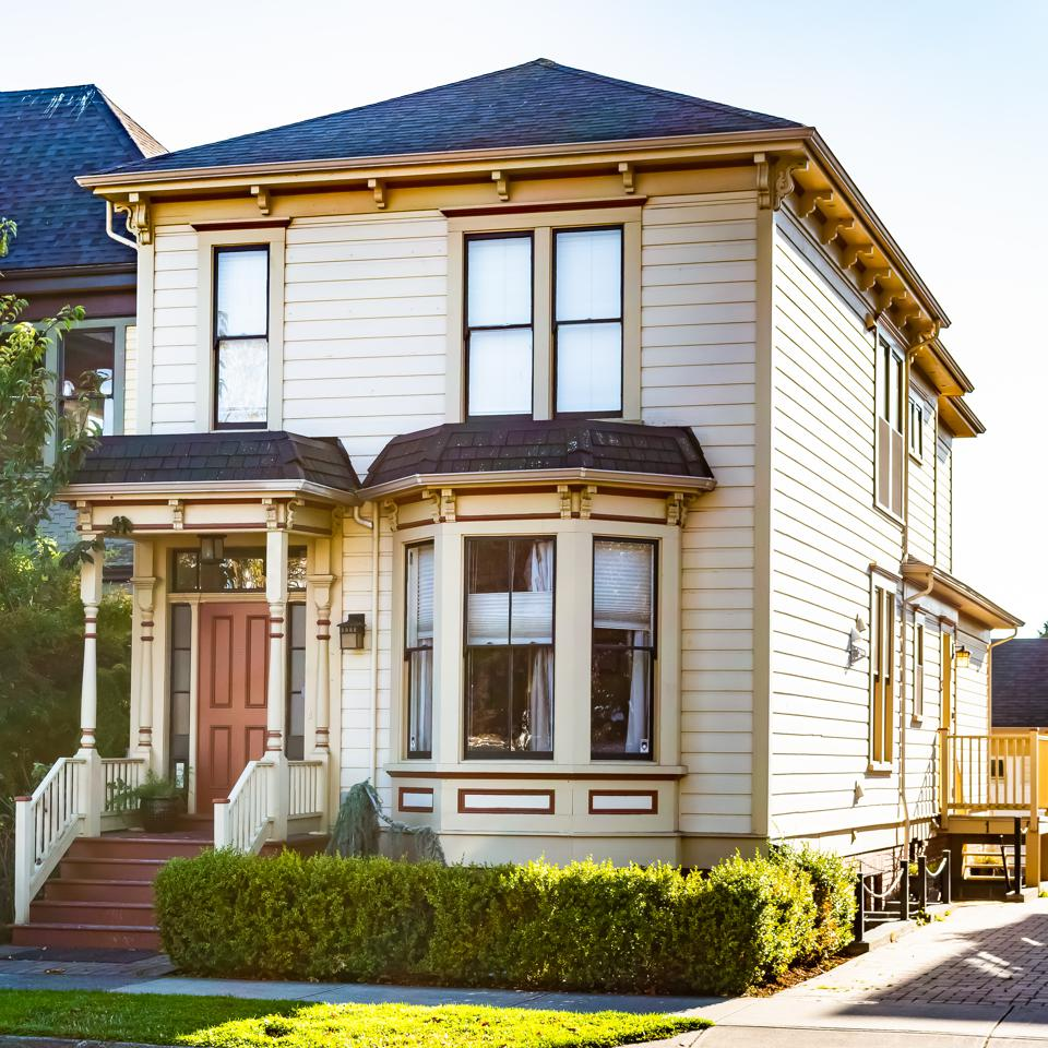 Semi detached two storey/ double floor townhouse with front porch in Victoria, Canada. Single family house/home. Real estate architecture.