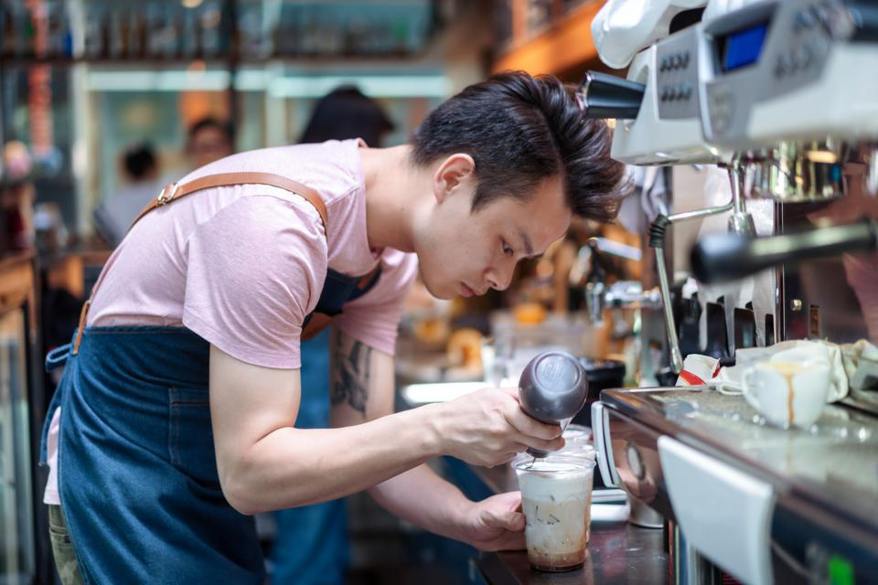 Asian Barista making coffee in the cafe