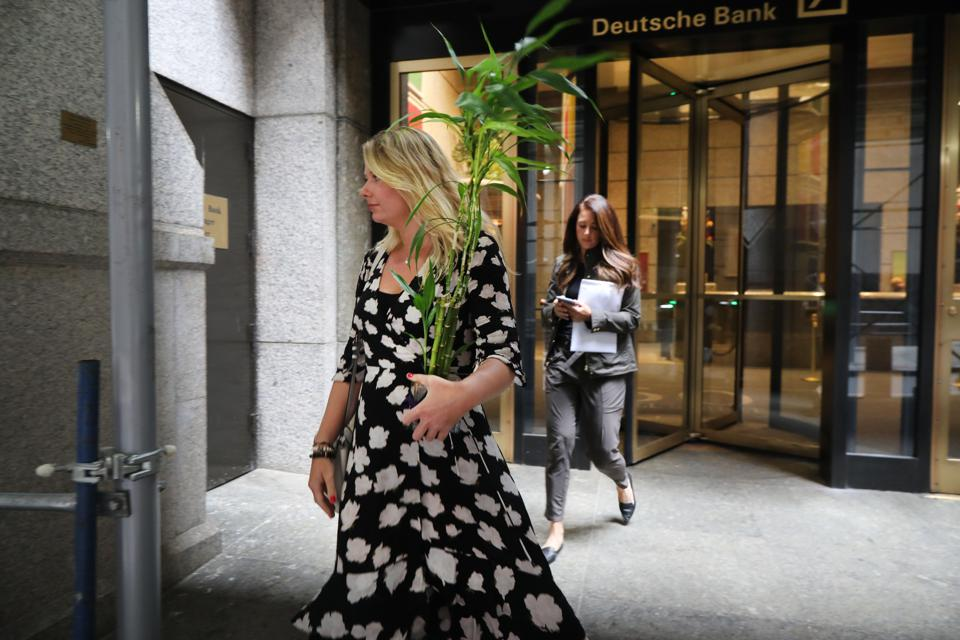 Two women exit the Deutsche Bank Wall Street office with personal belongings and the white envelopes containing severance packages.