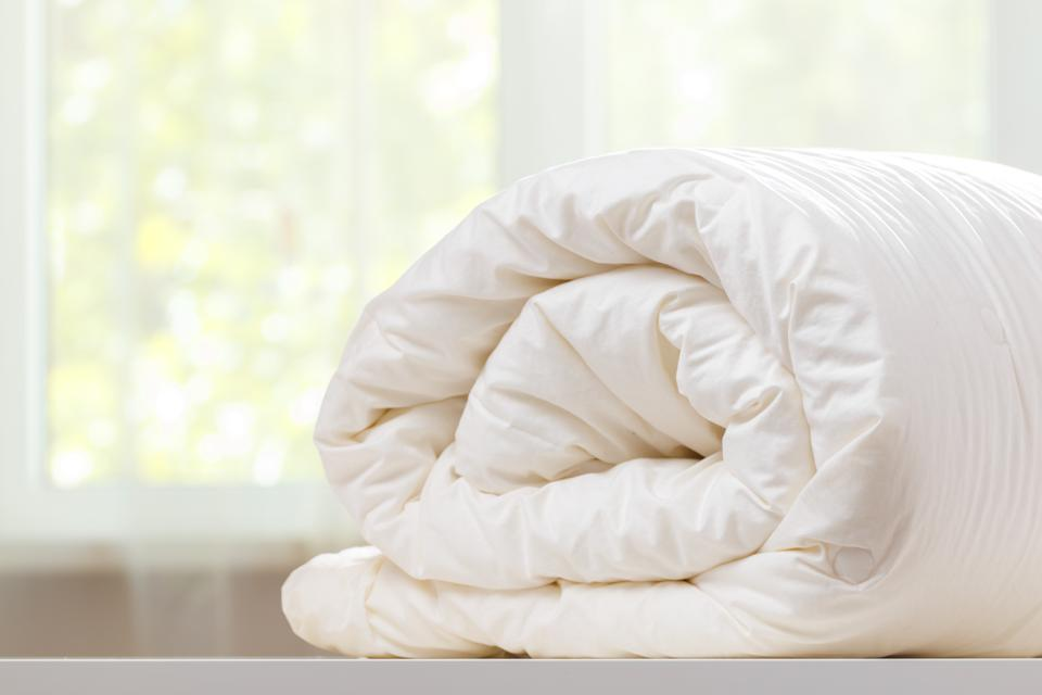 A folded rolls duvet is lying on the dresser against the background of a blurred window. Household.