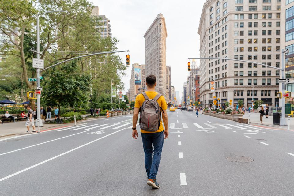 Young man walking on Fifth Avenue towards Flatiron Building in New York City