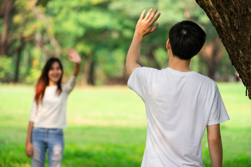 Two people waving hands in the park.