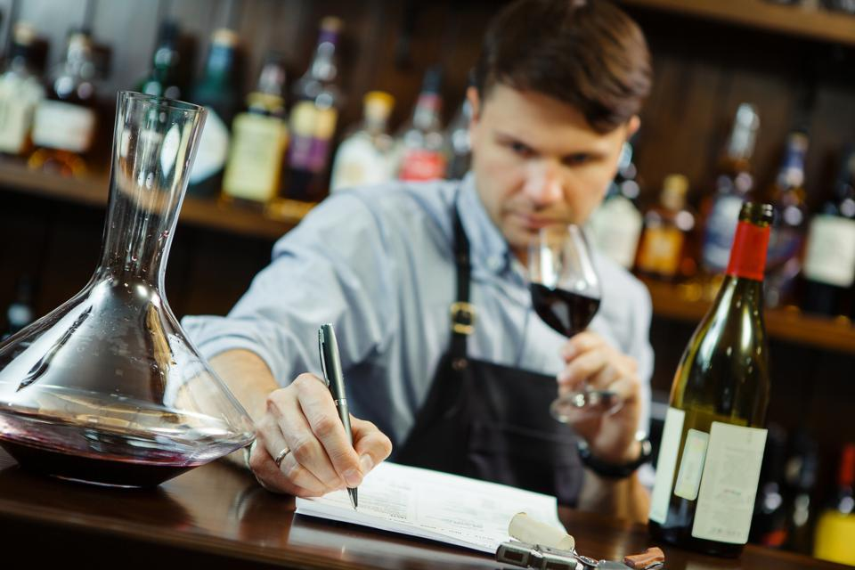 Sommelier  making notes at bar counter.