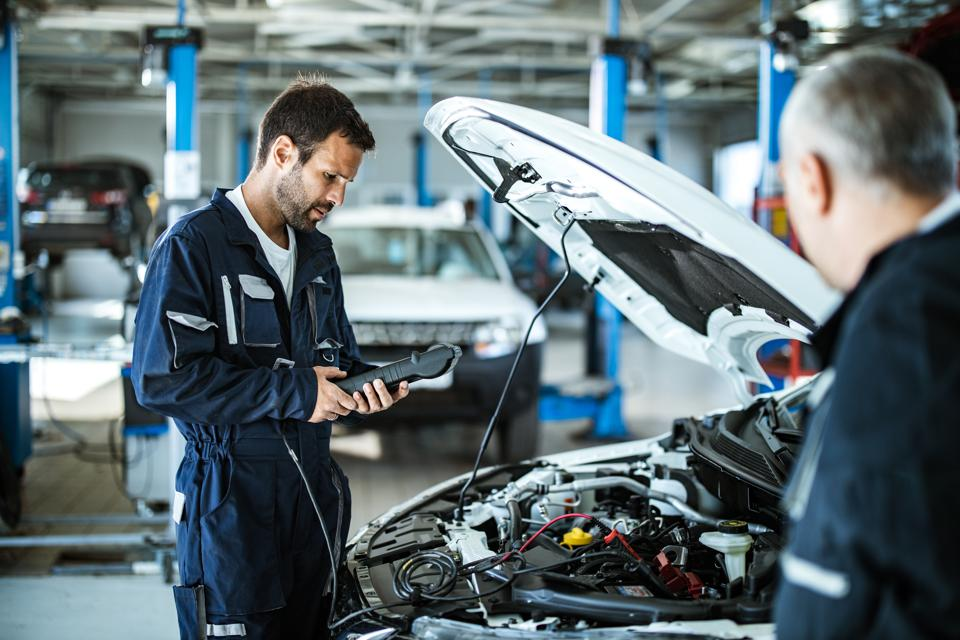 Auto mechanic working with car diagnostic tool in a repair shop.