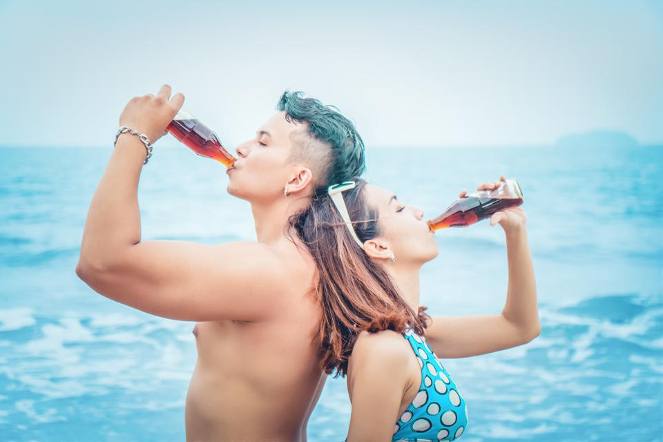 Side View Of Man And Woman Drinking Cola In Sea Against Sky