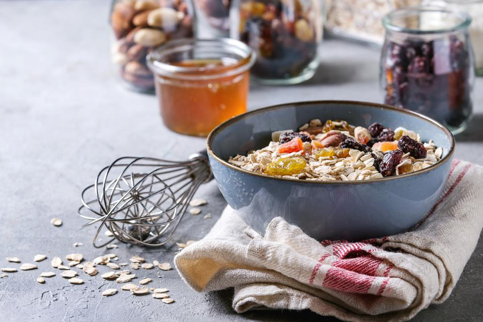 Variety of dried fruits. nuts. honey and oat flakes in bowl and different glass jars for cooking homemade healthy breakfast muesli or granola energy bars on grey blue table.