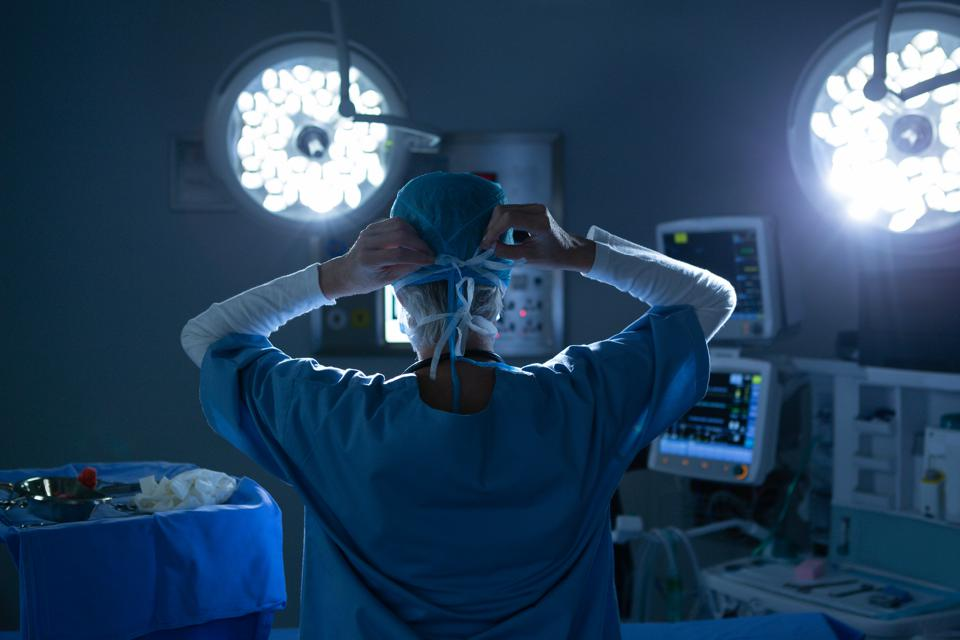 Female surgeon wearing surgical mask in operating room of hospital