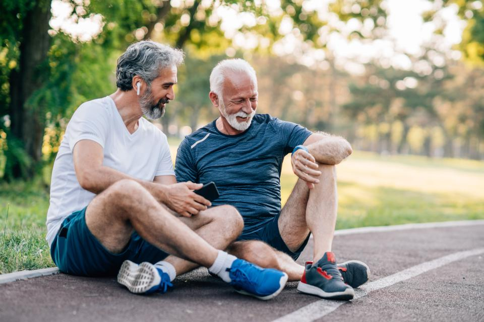 Smiling senior athletes relaxing after jogging in the park