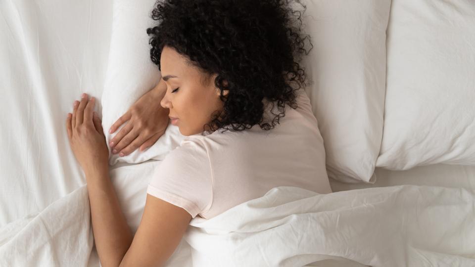 African American woman sleeping in bed, top view