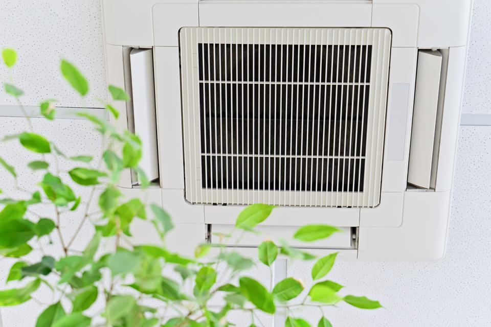Ceiling air conditioner in modern office or at home with green ficus leaves