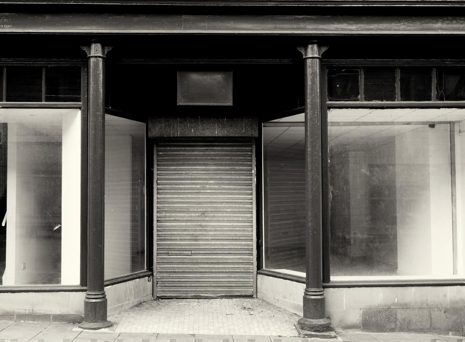 monochrome facade of an old abandoned shop with empty store front dirty windows and closed shutters on the door